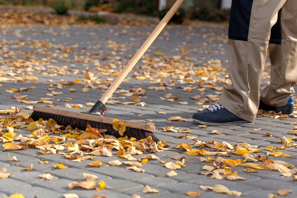 Worker cleaning up the driveway from autumn leaves.jpeg