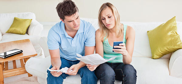 Concentrated young couple calculating bills sitting on the sofa in the living-room-2