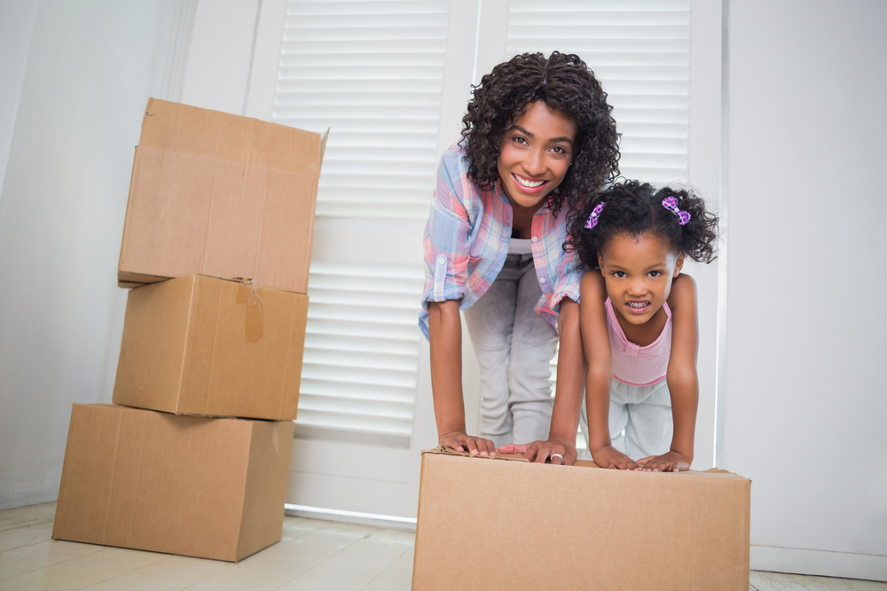 Cute daughter unpacking moving boxes with her mother in their new home