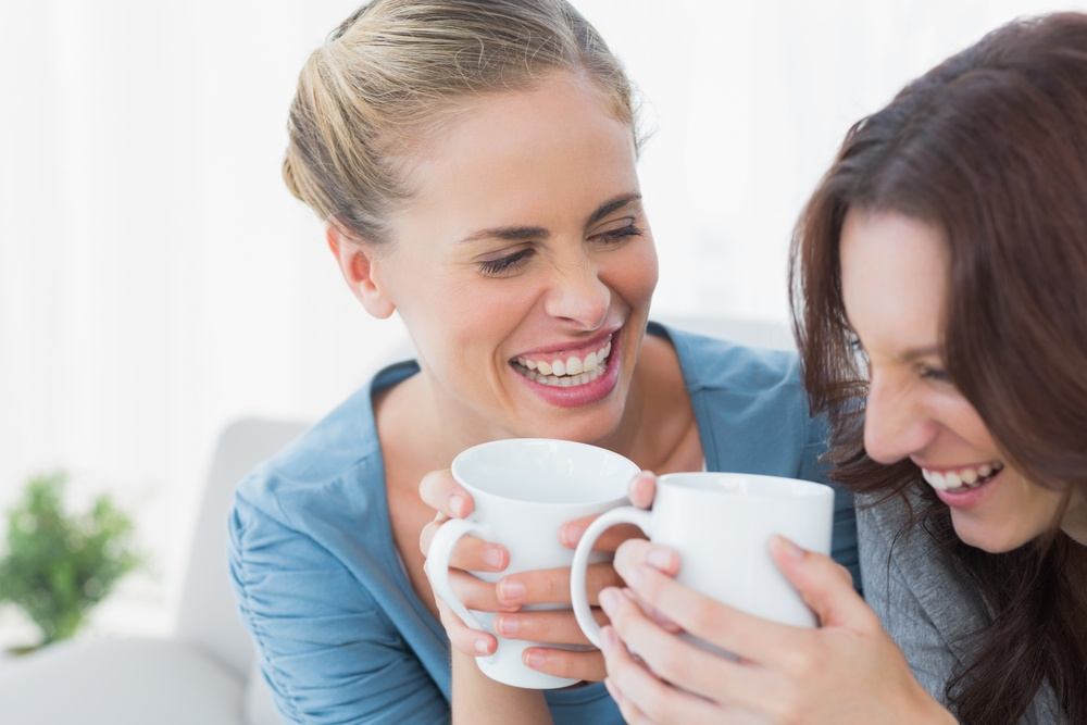 Friends bursting out laughing while having coffee sitting on the sofa.jpeg