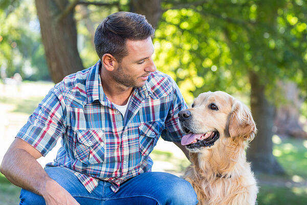 Happy man with his pet dog in park on a sunny day