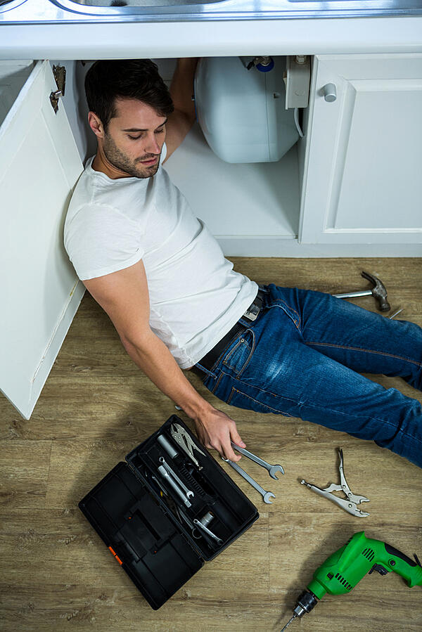 Man repairing a kitchen sink at home