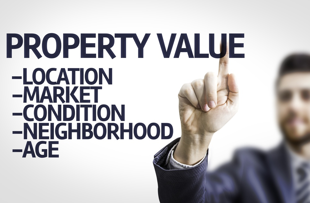 Business man pointing to transparent board with text Property Value .jpeg