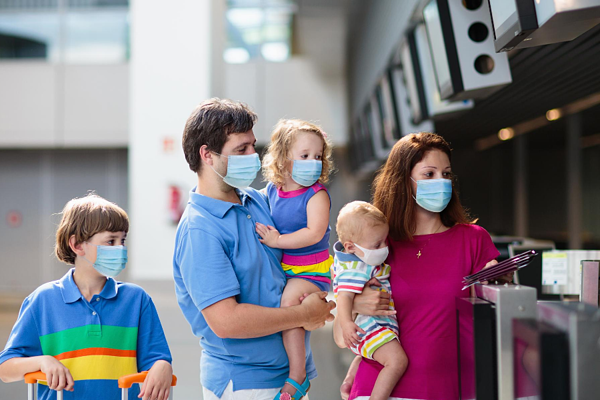 family wearing masks at airport
