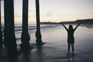 silhouette-of-woman-standing-with-arms-raised-in-the-water